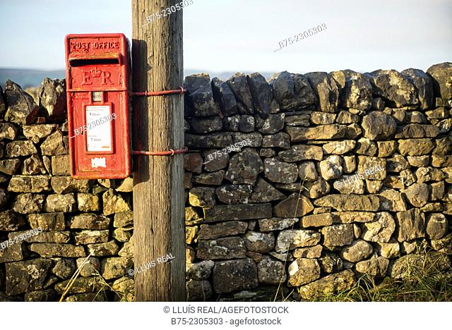 Closeup of a mailbox post, hanging from a pole with a stone wall in the background. Grassington, North Yorkshire, Yorkshire Dales, England, UK