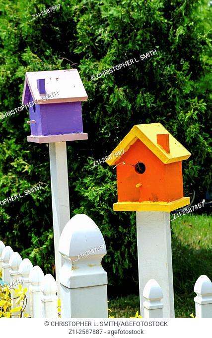 Multi-colored handmade birdhouses in a residential garden