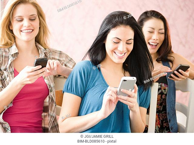 Friends text messaging on cell phones together