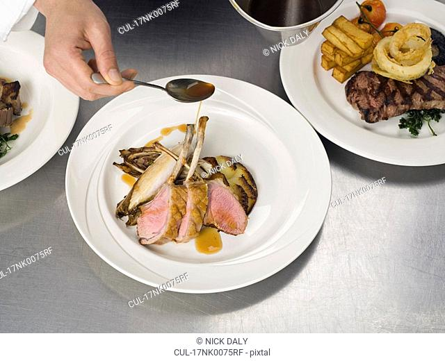 A hand drizzling gravy on some lamb