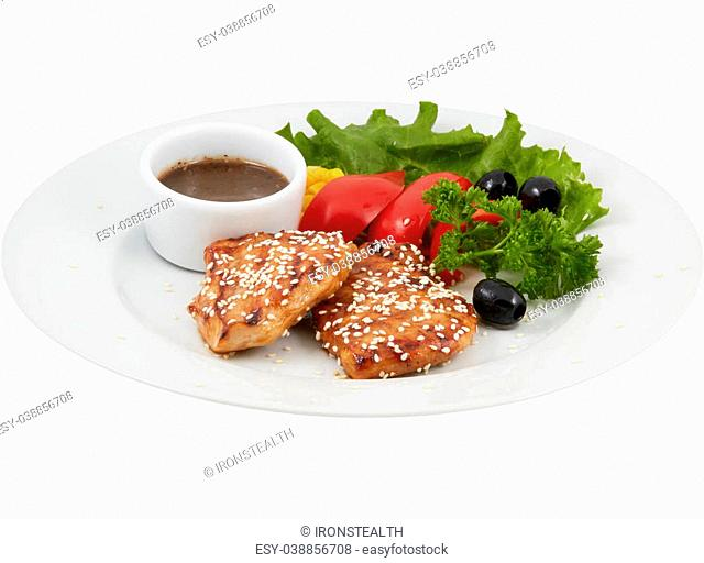 The medallions of fillet of chicken in a honey glaze on a on the plate with isolated background