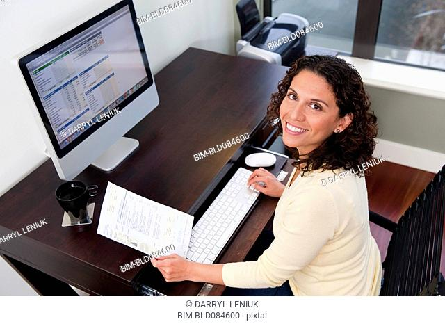 Hispanic woman paying bills on computer