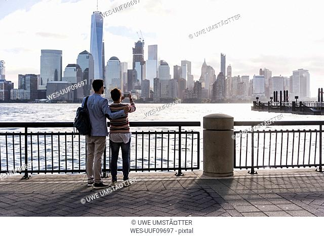 USA, man and woman at New Jersey waterfront with view to Manhattan