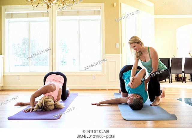 Caucasian couple working with yoga instructor in home