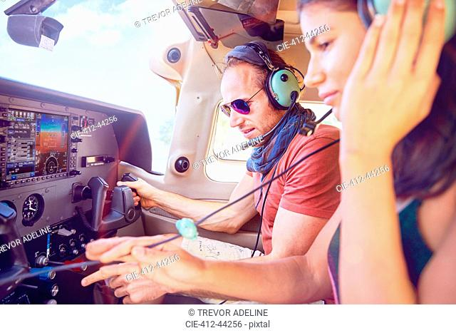 Pilot and copilot flying airplane, checking navigational equipment