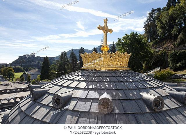 Guilded crown and cross on the dome of the Rosary Basilica of the Sanctuary of Our Lady of Lourdes