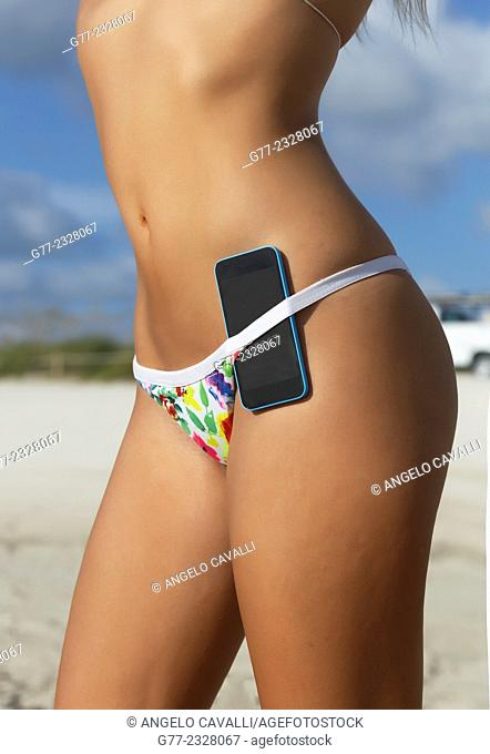 Young woman on the beach with smartphone in the swimsuit. Miami Beach, Florida, USA
