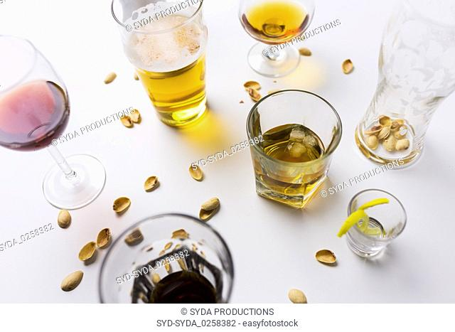 glasses of different alcohol drinks on messy table