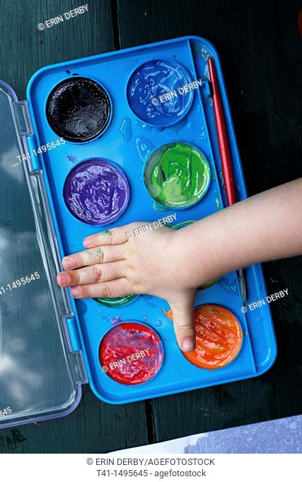 A child's hand over a palette of water colors