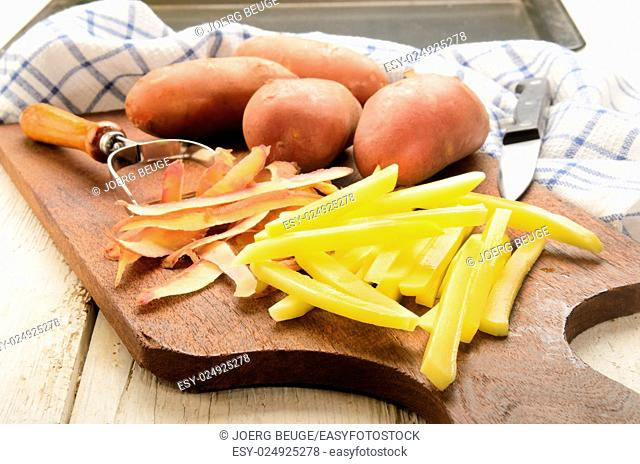 freshly cut raw french fries on a wooden board and peeler
