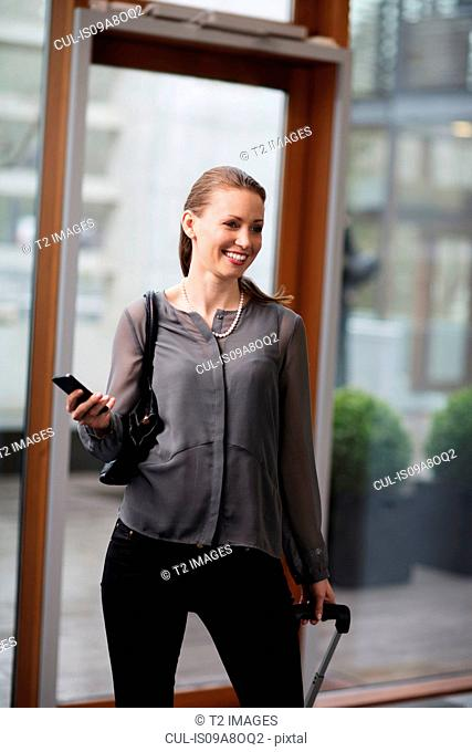 Woman holding mobile phone entering office