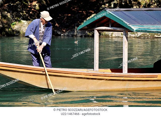 Kyoto (Japan): a sailor taking tourists on excursion on a small boat in Arashiyama