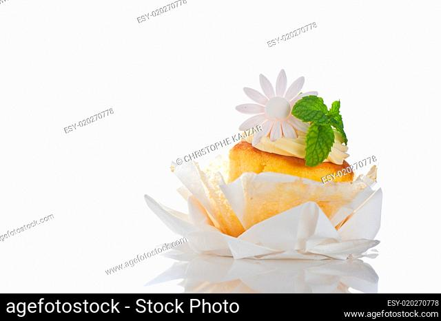 Cupcake with vanilla cream mint leaf and sugar flower on a white