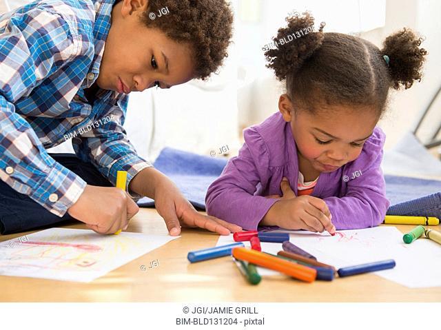 Black children coloring on living room floor