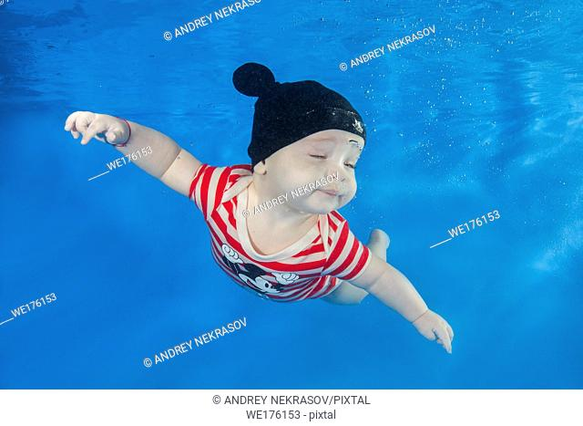 Little boy in a striped suit swim underwater in the swimming poo on a blue water background. Healthy family lifestyle and children water sports activity