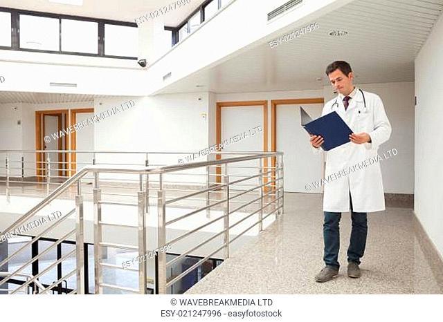 Doctor checking folder in hospital corridor