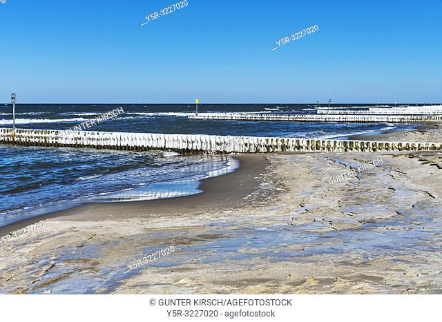 Beach of the Baltic Sea at Kolberg in winter. | Ice covered Groynes are in the water. Groynes are intended to break the shaft and to prevent the erosion of the...