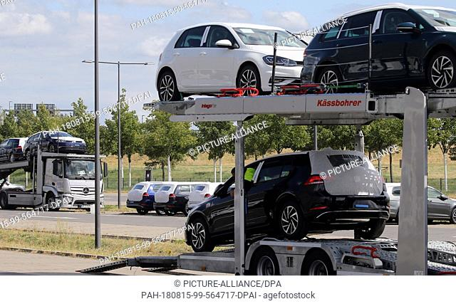 15 August 2018, Germany, Schoenefeld: Unauthorised Volkswagen vehicles are unloaded by car transporters at a parking lot at BER Airport in Schoenefeld near...