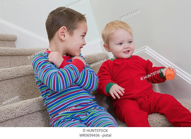 Boy signing the word Love in American Sign Language while communicating with his brother
