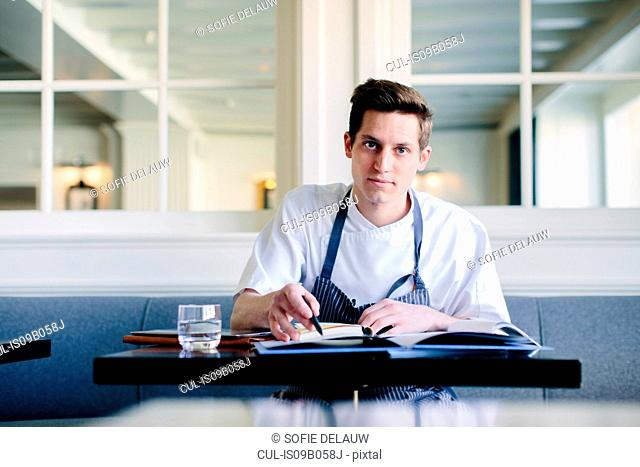 Portrait of young male chef writing up menu in restaurant