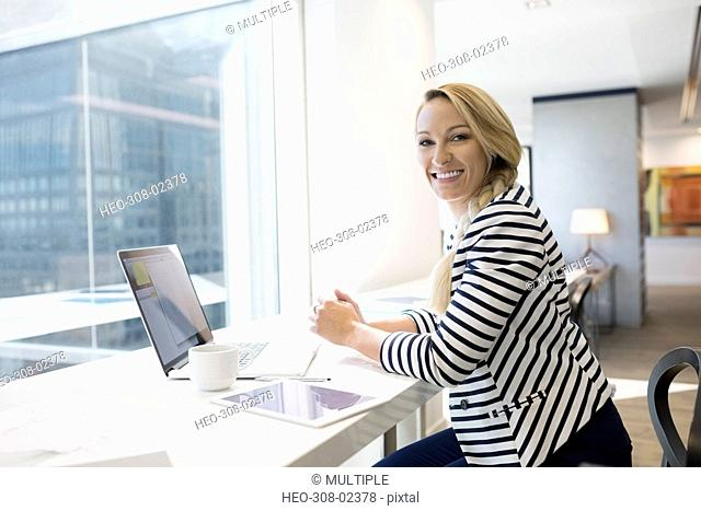 Portrait smiling businesswoman working at laptop at urban office window