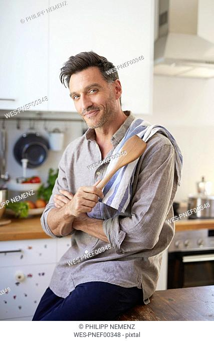 Portrait of smiling man with cooking spoon in the kitchen