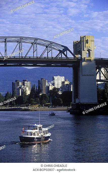 Burrard bridge frames view to West End, with small passenger ferry, Vancouver, British Columbia, Canada