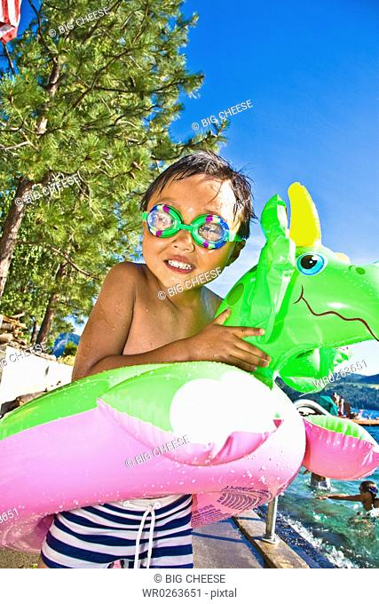boy with dragon floatie and goggles
