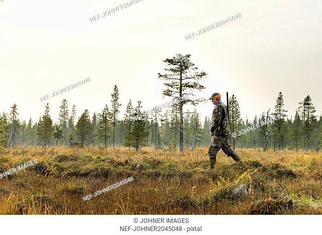 Hunter walking through meadow