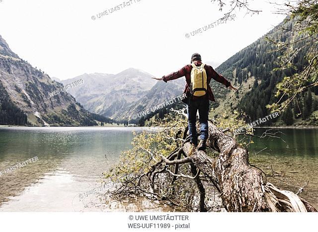 Austria, Tyrol, Alps, hiker balancing on tree trunk at mountain lake