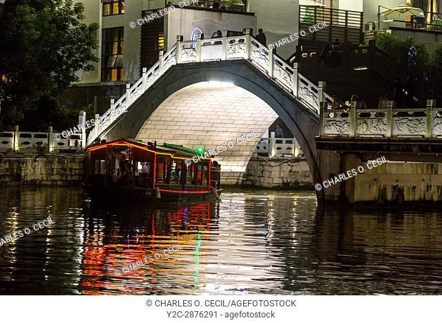 Wenzhou, Zhejiang, China. Tourist Boat Passing under Bridge Over the Nantong River, at Night