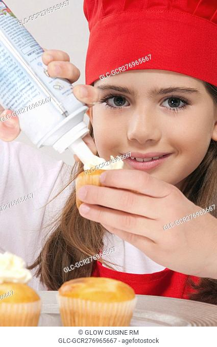 Portrait of a girl putting whipped cream on cupcakes