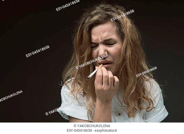 Portrait of woman inhaling coffin nail fume and expressing dissatisfaction. Copy space in left side. Isolated on background
