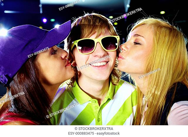 Two happy girls kissing smiling guy during party