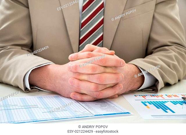 Close-up Of Businessman With Hands Clasped Over Gantt Chart