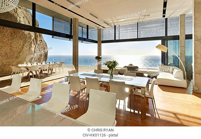 Modern luxury home showcase dining room and living room with sunny ocean view