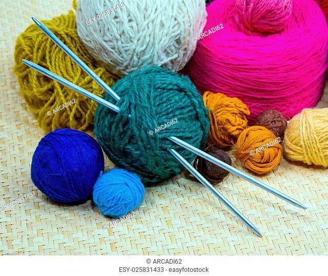 colored yarn for knitting with spokes in a basket on a yellow matting. macro, still life