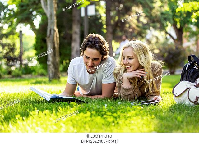A young couple lays down studying on the grass on the university campus looking through a textbook and using a tablet; Edmonton, Alberta, Canada