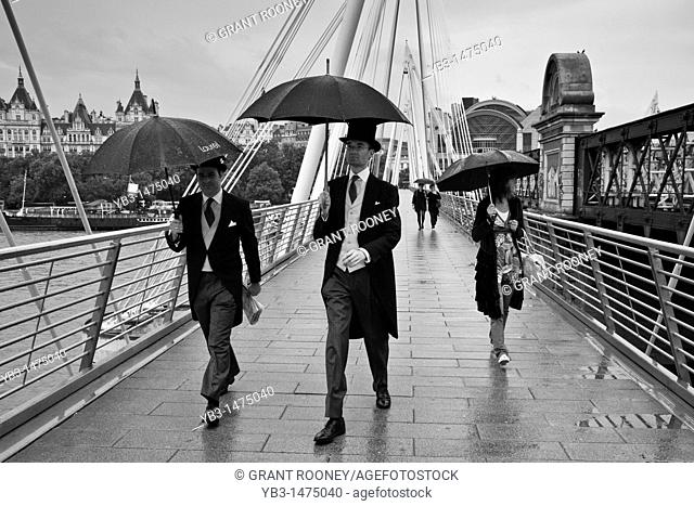Two men dressed in suits cross Hungerford/Golden jubilee bridge on their way to Royal Ascot, London, England