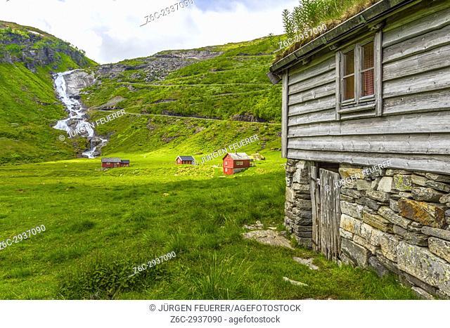 Waterfall Sendefossen, red wooden houses and the Serpentinveg near Myrkdalen, Vikafjell region, Norway, Scandinavia