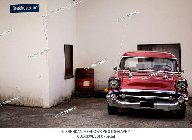 Vintage burgundy car parked outside house, Seyoisfjorour, Iceland