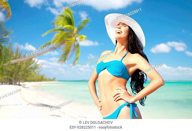 people, summer holidays, vacation and travel concept - happy young woman posing in bikini swimsuit and hat over exotic tropical beach with palm trees and sea...