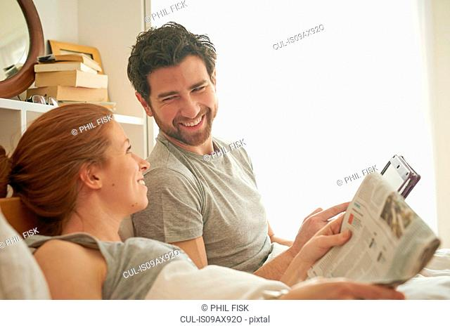 Mid adult couple reading broadsheet and digital tablet in bed