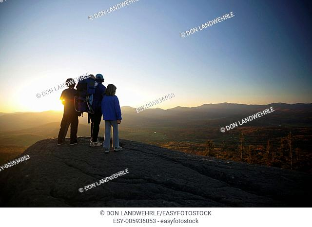 Family watching sunset on top of The Pinnacle, Stowe, Vermont, USA