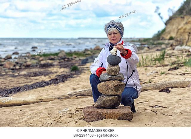 Woman building a cairn on the beach, Timmendorf on the Island of Poel, Mecklenburg-Western Pomerania, Germany, Europe