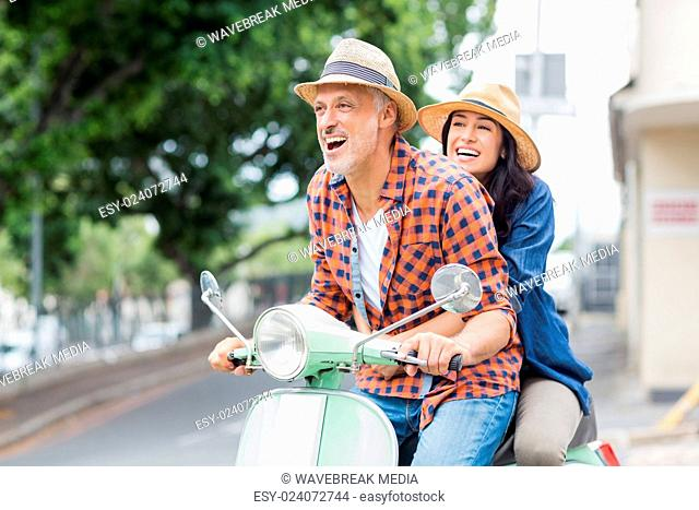 Excited couple riding moped