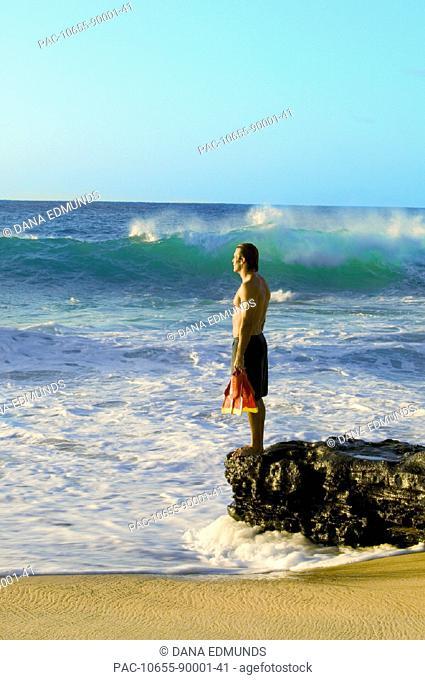 Hawaii, Oahu, Sandy Beach, Bodysurfer stands on rocks looking at ocean, holding fins