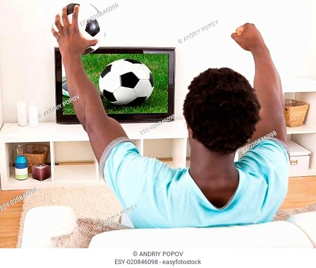 African Young Man Watching Television Holding Football