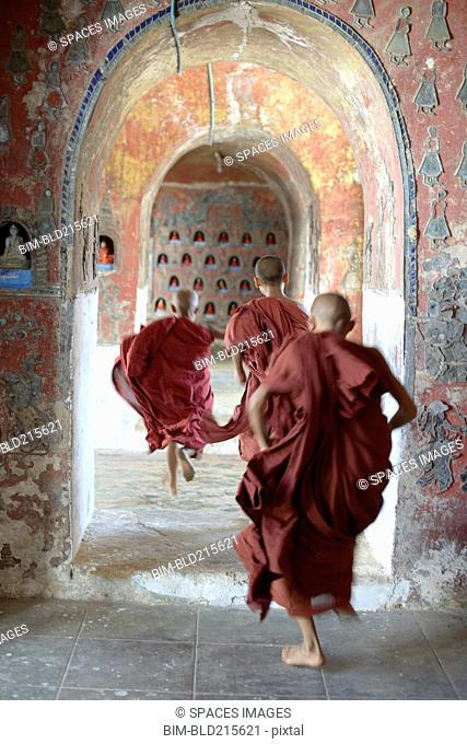 Asian monks-in-training running in dilapidated temple hallway
