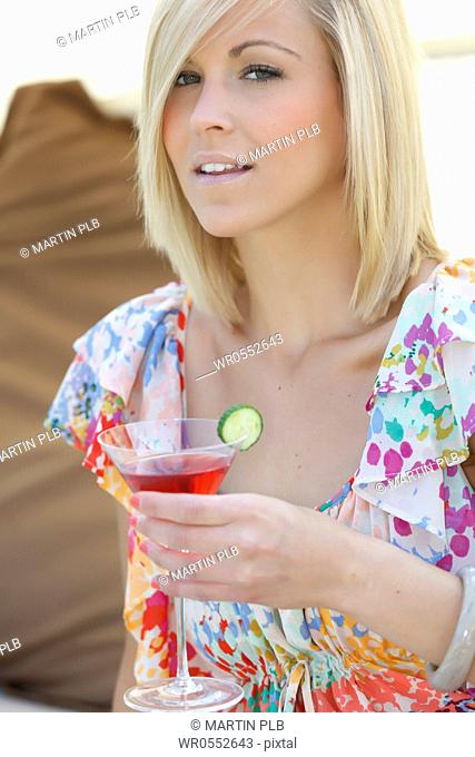 beautiful young woman relaxing with cocktail in garden lounge